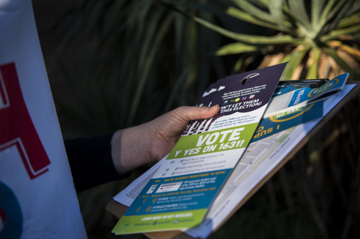 Heidi Cody, a climate change activist, comes equipped with literature in support of Initiative 1631.