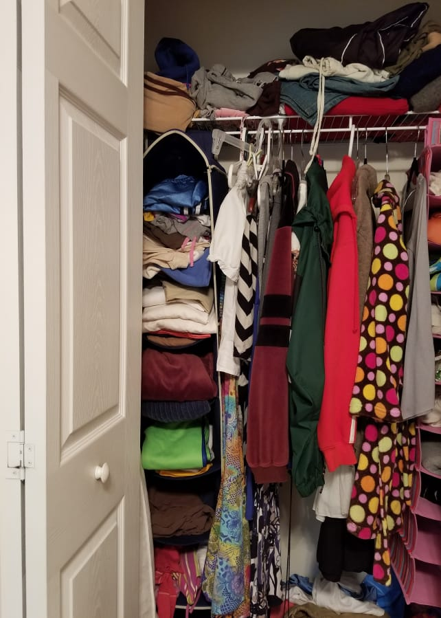 80e89fd3dae32 The small storage space: closet with clothes on a hangers, on a shelved,