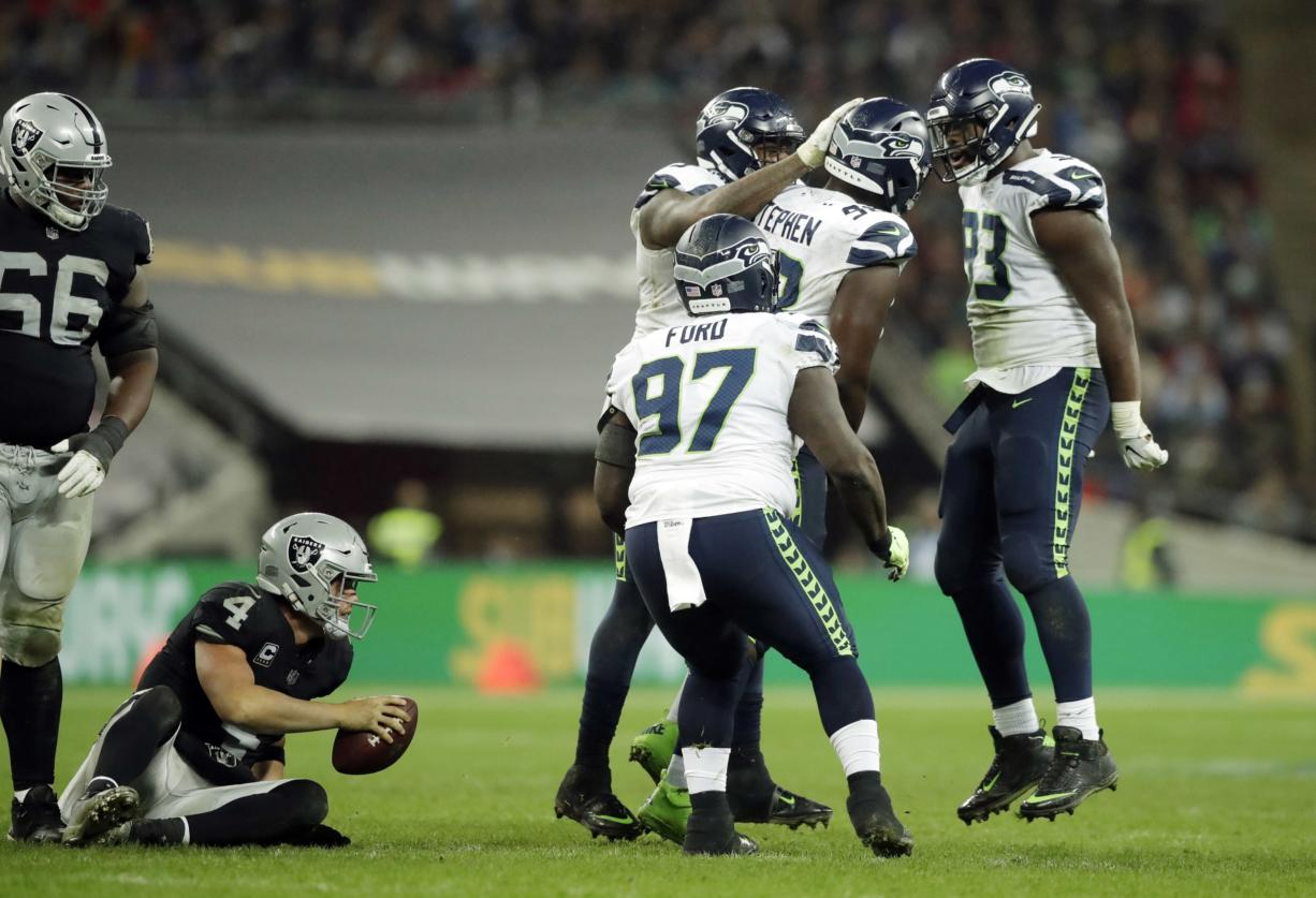 Seattle Seahawks players react after sacking Oakland Raiders quarterback Derek Carr (4), bottom left, during the second half of an NFL football game at Wembley stadium in London, Sunday, Oct. 14, 2018.