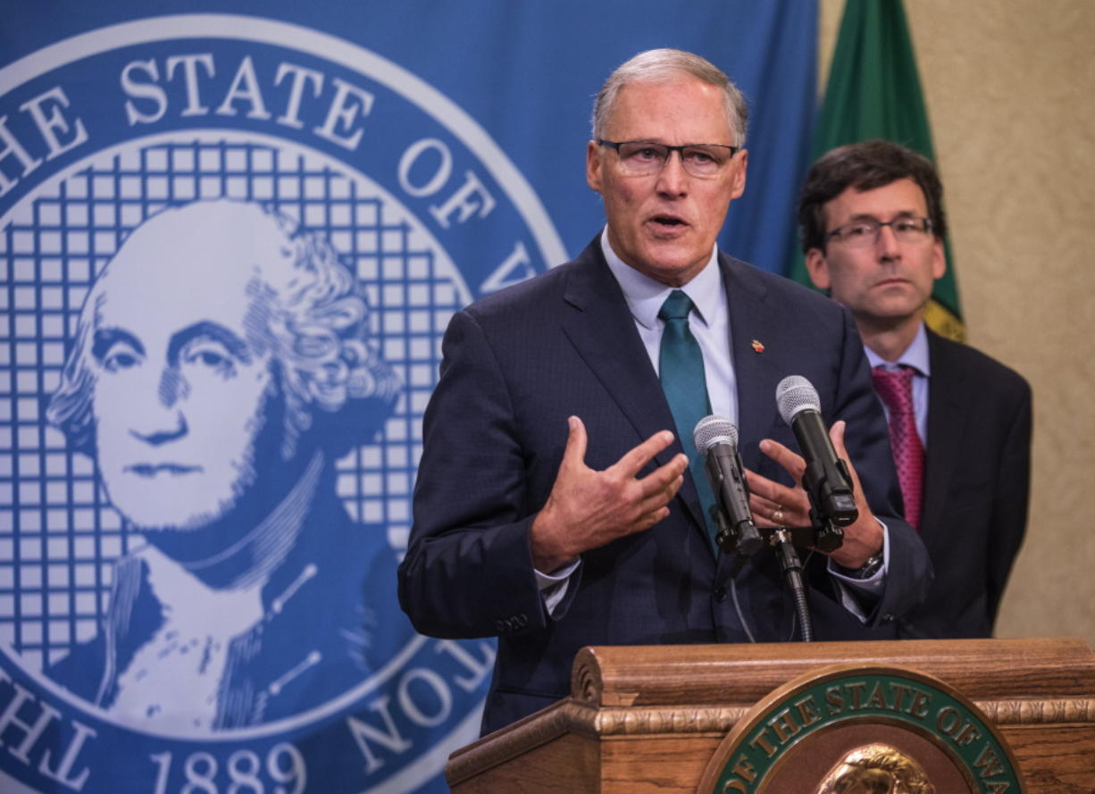 Gov. Jay Inslee addresses a news conference Thursday in Olympia with Attorney General Bob Ferguson following an earlier announcement that Washington's Supreme Court struck down the state's death penalty. steve ringman/The Seattle Times