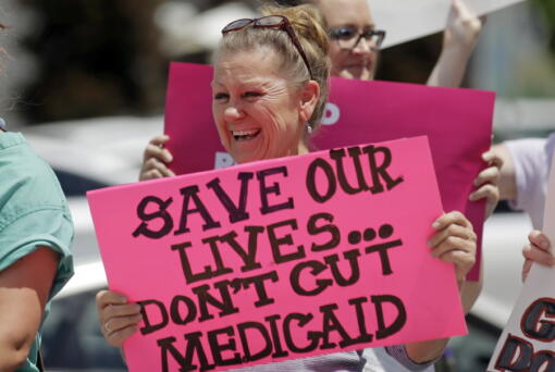 FILE - In this June 27, 2017 file photo, protesters block a street during a demonstration against the Republican bill in the U.S. Senate to replace former President Barack Obama's health care law, in Salt Lake City.