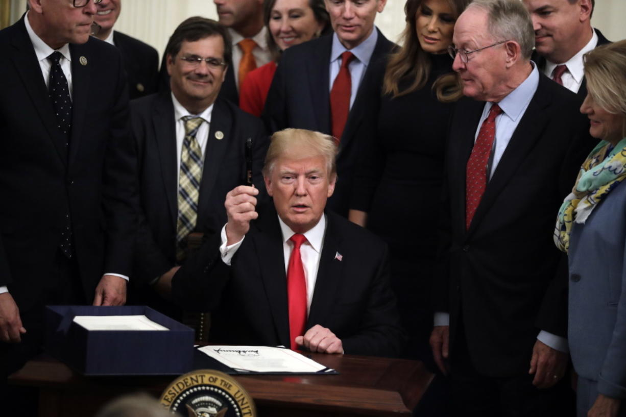 President Donald Trump holds up a pen in the East Room of the White House on Wednesday after signing bipartisan legislation to confront the opioid crisis.