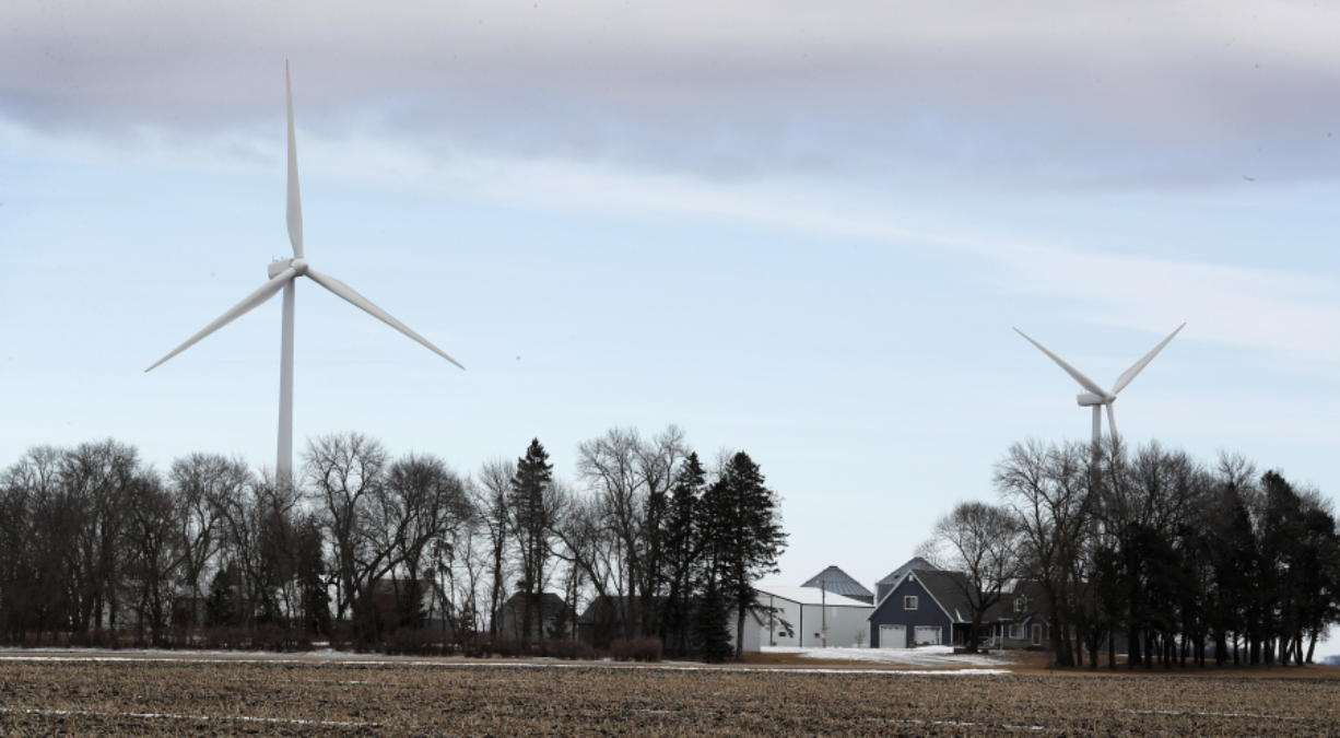 Wind turbines stand over a farmhouse near Northwood, Iowa. A new study out of Harvard finds that ramping up wind power in America would also dial up the nation's temperatures.
