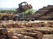 A log loader picks up a load of timber from a truck in a scaling and sorting area at Columbia Vista Corp in 2014.(The Columbian files)