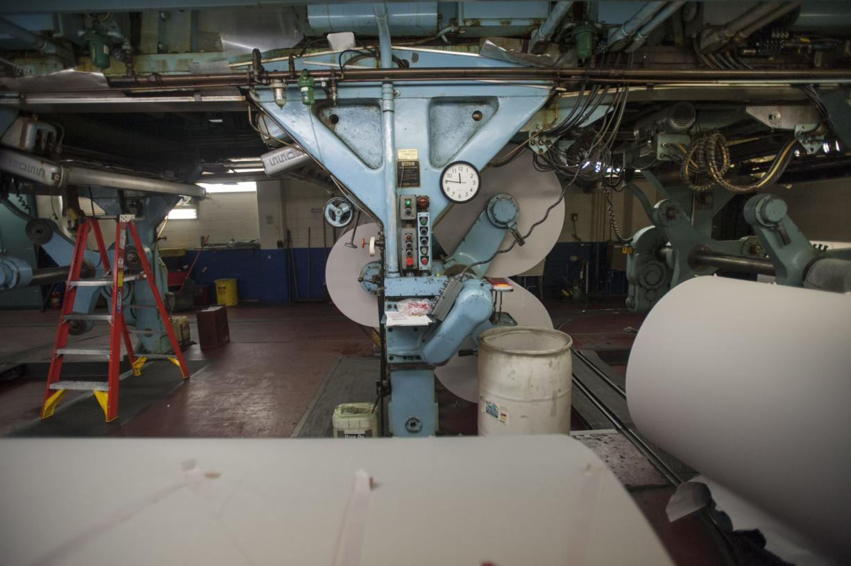 Newsprint arrives on big rolls, which are attached to the underside of The Columbian''s Goss Metro offset press.