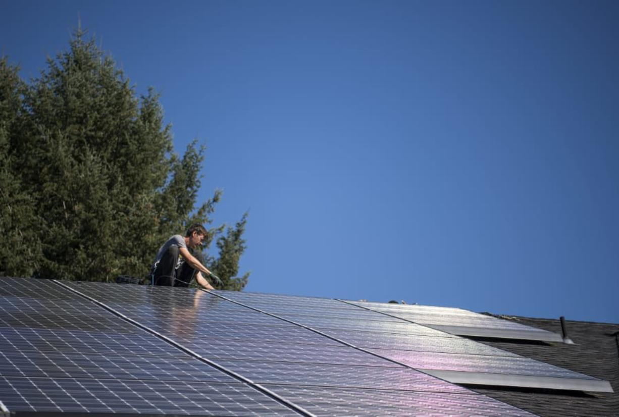 Simon Petersen, roof lead and apprentice electrician at Tesla, wires a solar array on the roof at Mike Burton's home in September in Vancouver. Burton hopes to connect his solar array to a battery system that will allow him to store power.