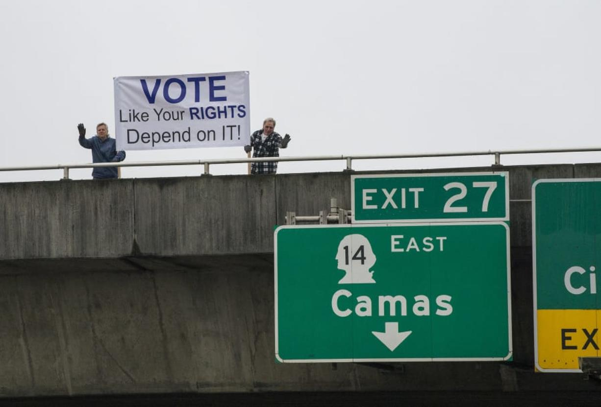 Vancouver residents Alan Pasternak, left, and Jim Walker encourage residents to vote while greeting motorists traveling south on Interstate 205 from the southeast 10th Street overpass Tuesday morning, Oct. 30, 2018. (Amanda Cowan/The Columbian)