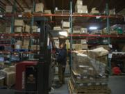 Cesar Hernandez of Price Mart, the warehouse in Portland used by Hi-School Pharmacy, helps distribute stock as he works with colleagues in early November.