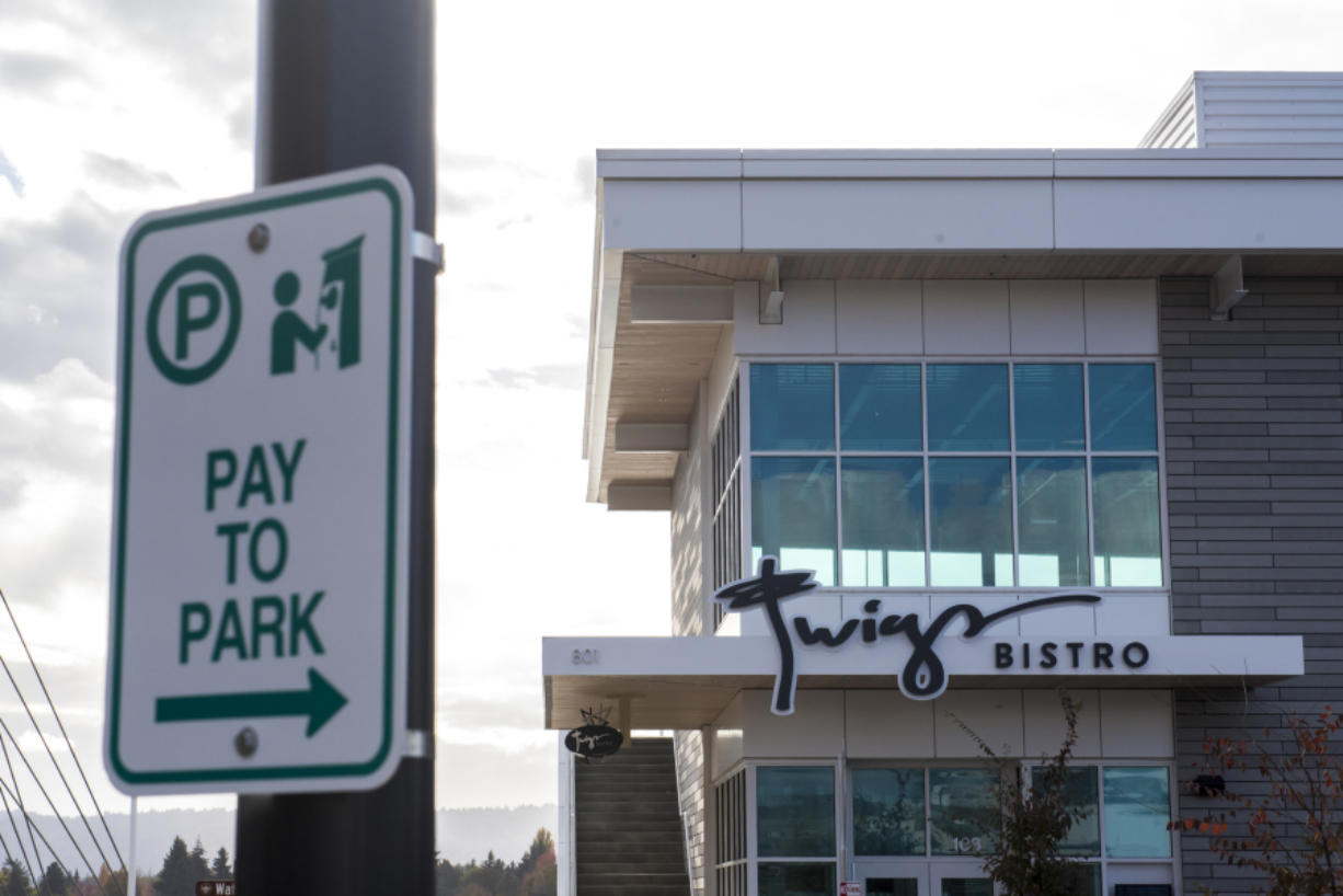 A sign notifying drivers they need to pay to park is seen in front of Twigs Bistro on Tuesday.