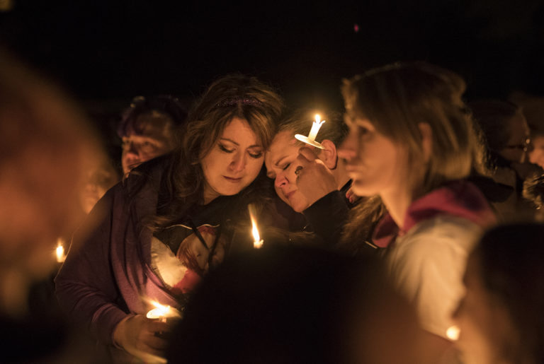 Tomisa Bates, left, and Sheila Crosslin share a quiet moment with the crowd during a candlelight vigil in honor of Hartley Anderson, 5, at LeRoy Haagen Memorial Park on Friday evening, Nov. 9, 2018.