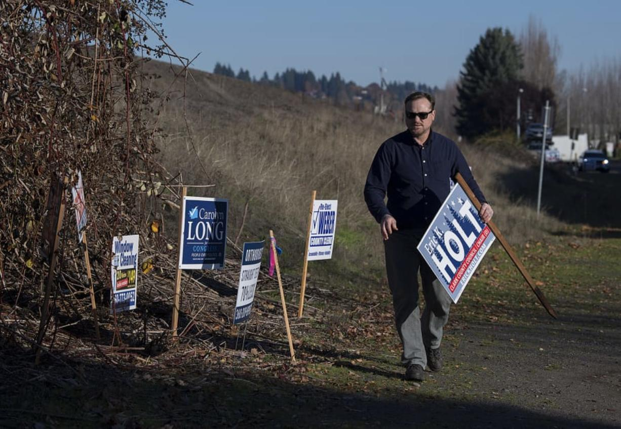 Eric Holt, who campaigned for Clark County Council chair, collects his signs after the election along Southeast Columbia Way in Vancouver on Thursday afternoon.