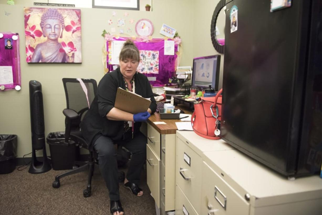 Ronda J. Harrison, care navigator at the Veterans Affairs Rapid Response Clinic in Vancouver, checks a patient's chart.