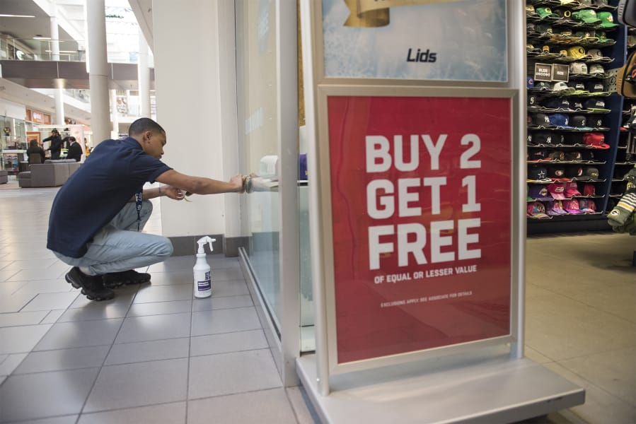 a6e46b4057ade Lids sales associate Tavi Pikmey cleans the store window Monday at  Vancouver Mall. Nathan Howard