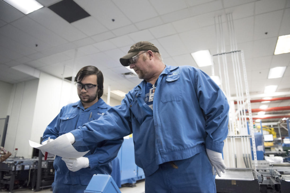 Nathaniel Salveta, left, takes direction from process technician Randall Chromey at Shin-Etsu Handotai (SEH) America on Wednesday afternoon. Salveta is enrolled in the Manufacturing Career Launch program, which will allow him to pursue a degree in mechatronics while working at SEH America.