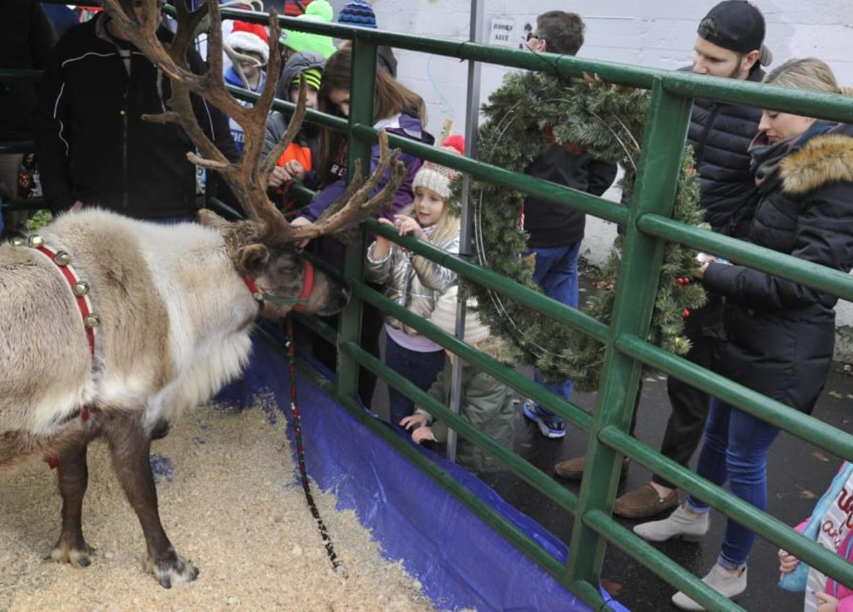 Joni Zimmerman, center, visits reindeer at the 2016 Uptown Christmas in the Village Block Party.