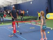 James Blake hit tennis balls with kids during a community event at the Vancouver Tennis Center on Saturday, Nov. 3, 2018.