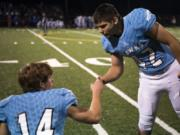 Hockinson's Levi Crum (14) and Jon Domingos (42) encourage each another before the first round of the 2A state football playoffs against Washington.