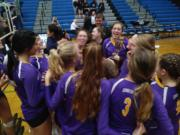 The Columbia River volleyball team gathers around the district championship trophy after taking the title Saturday in Hockinson (Tim Martinez/The Columbian)