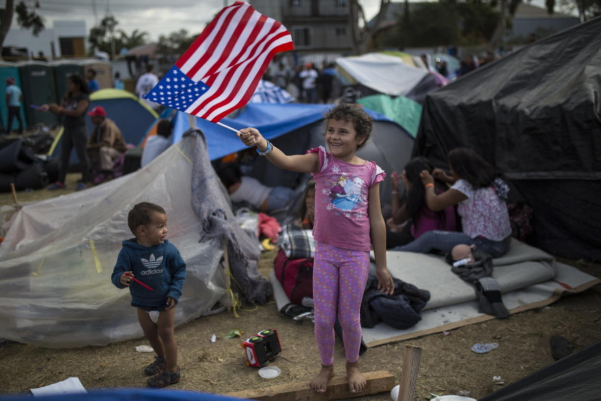 Honduran migrant Genesis Belen Mejia Flores, 7, waves an American flag at U.S. border control helicopters flying overhead Saturday near the Benito Juarez Sports Center in Tijuana, Mexico, which is serving as a shelter for migrants.