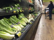 FILE - In this Nov. 20, 2018 file photo, romaine lettuce sits on the shelves as a shopper walks through the produce area of an Albertsons market in Simi Valley, Calif. After repeated food poisoning outbreaks linked to romaine lettuce, the produce industry is confronting the failure of its own safety measures in preventing contaminations. The latest outbreak underscores the challenge of eliminating risk for vegetables grown in open fields and eaten raw. It also highlights the role of nearby cattle operations and the delay of stricter federal food safety regulations. (AP Photo/Mark J.
