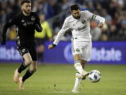 Portland Timbers midfielder Diego Valeri (8) shoots on net ahead of Sporting Kansas City midfielder Ilie Sanchez, left, during the first half in the second leg of the MLS soccer Western Conference championship in Kansas City, Kan., Thursday, Nov. 29, 2018.
