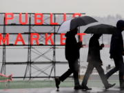 Pedestrians huddle under rain hoods and umbrellas as they pass a sign at the Pike Place Market during a steady rain Monday, Nov. 26, 2018, in Seattle.