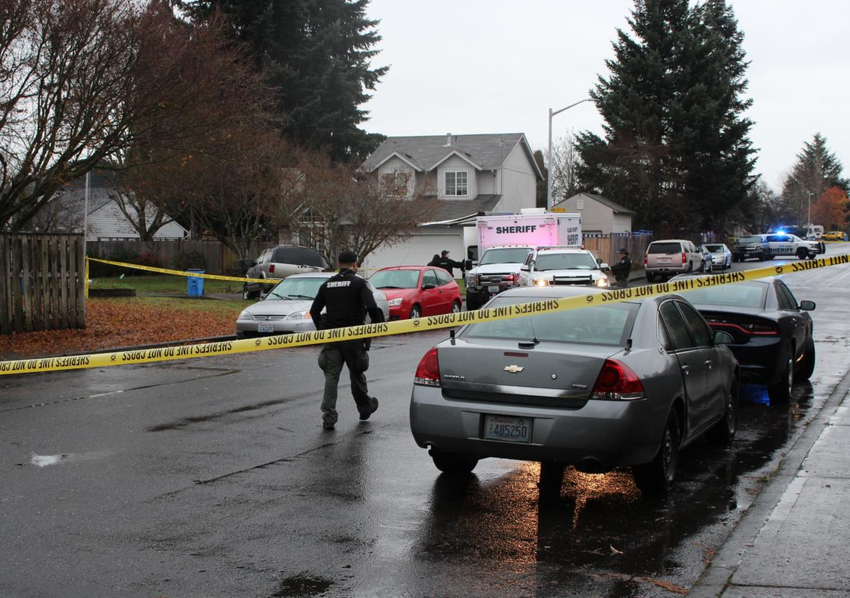 A sheriff's deputy approaches the scene of a deputy-involved shooting Wednesday morning in the Orchards area. The Clark County Sheriff's Office said a deputy was rammed by a stolen vehicle suspect.