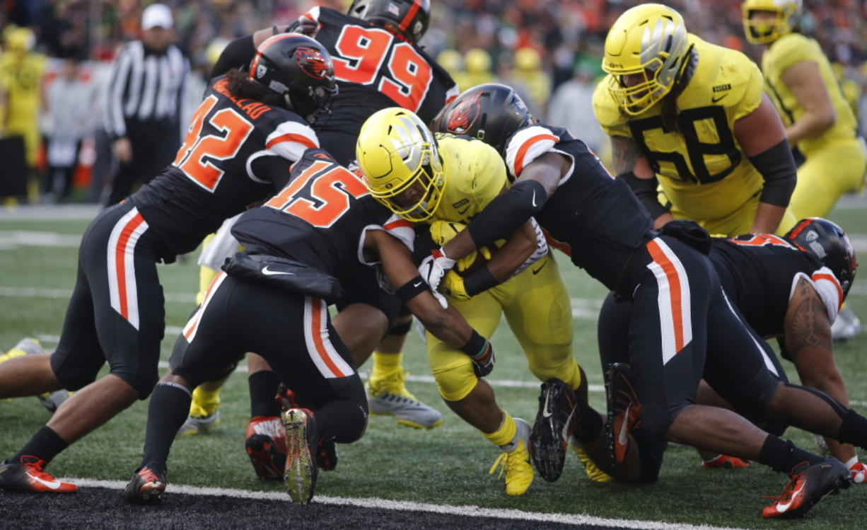 Oregon running back C.J. Verdell, center, bulls his way past Oregon State's Doug Taumoelau (42), Jeffrey Manning Jr. (15) and Hamilcar Rashed Jr (right) for a touchdown in the first half of an NCAA football game in Corvallis, Ore., on Friday, Nov. 23, 2018. (AP Photo/Timothy J.