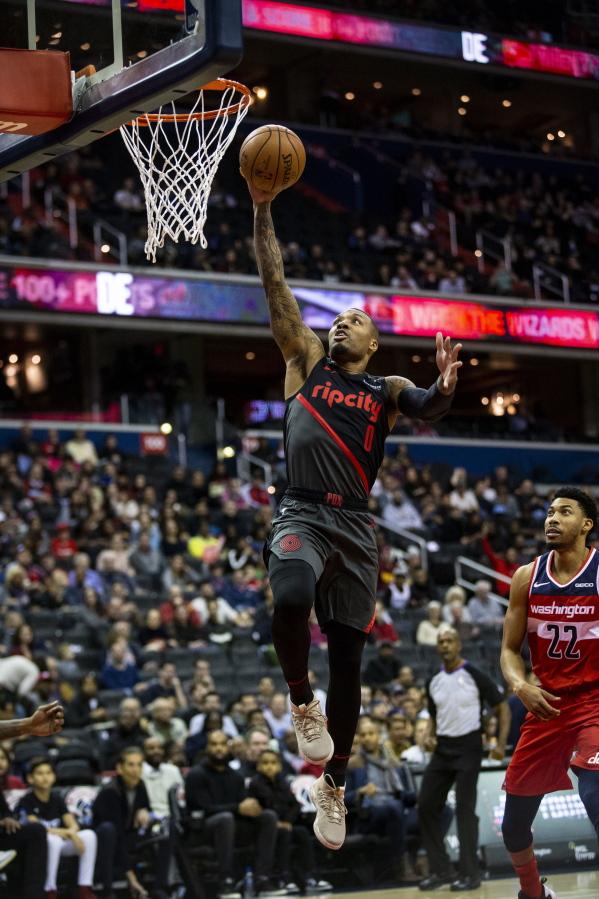 Portland Trail Blazers guard Damian Lillard (0) makes a layup past  Washington Wizards forward