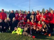 The Camas girls soccer team poses with coach Roland Minder after a 4-2 win over Bellarmine Prep in the 4A state quarterfinals at Doc Harris Stadium. On Saturday, Nov. 10, 2018.