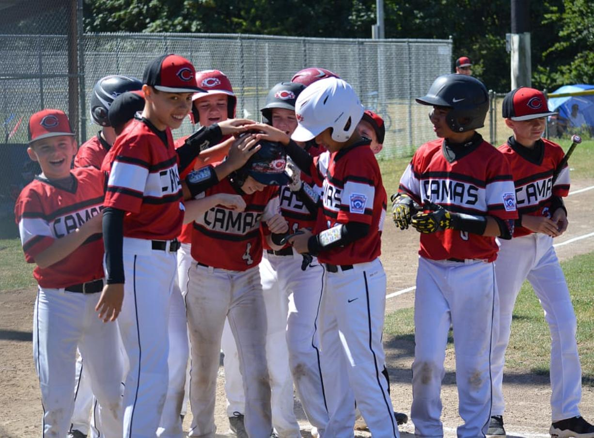 (Files/The Columbian) Jackson Knuth gets patted down by his teammates at home plate after hitting a 3-run home run for the Camas Little League Major all-star baseball team last summer at David Douglas Park in Vancouver.