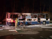 Firefighters inspect the remains of a motor home destroyed in a fire Tuesday night at the southbound Gee Creek rest area off Interstate 5.