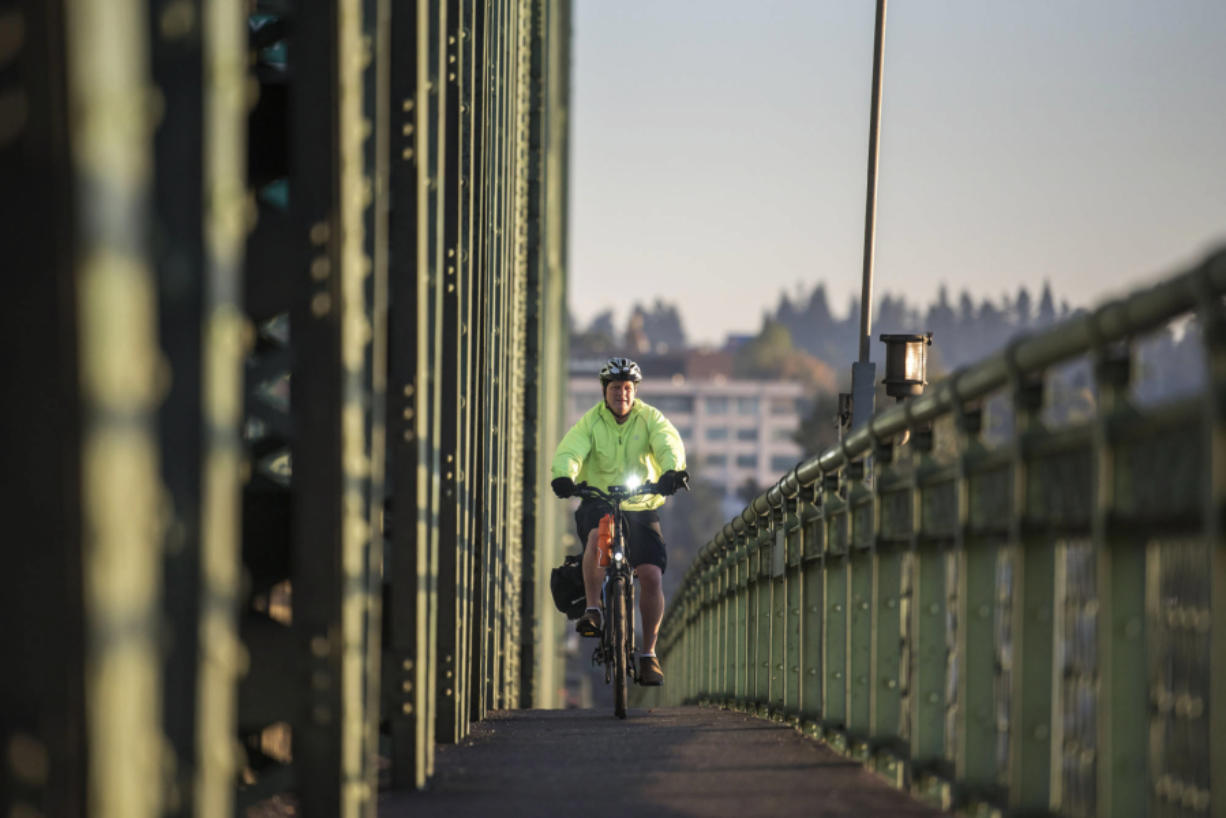 Dan Herrigstad rides his e-bike across the Interstate 5 Bridge as part of his morning commute from his east Vancouver home to the Portland Veterans Affairs Medical Center near the Oregon Health and Science University campus. Photos by Nathan Howard/The Columbian