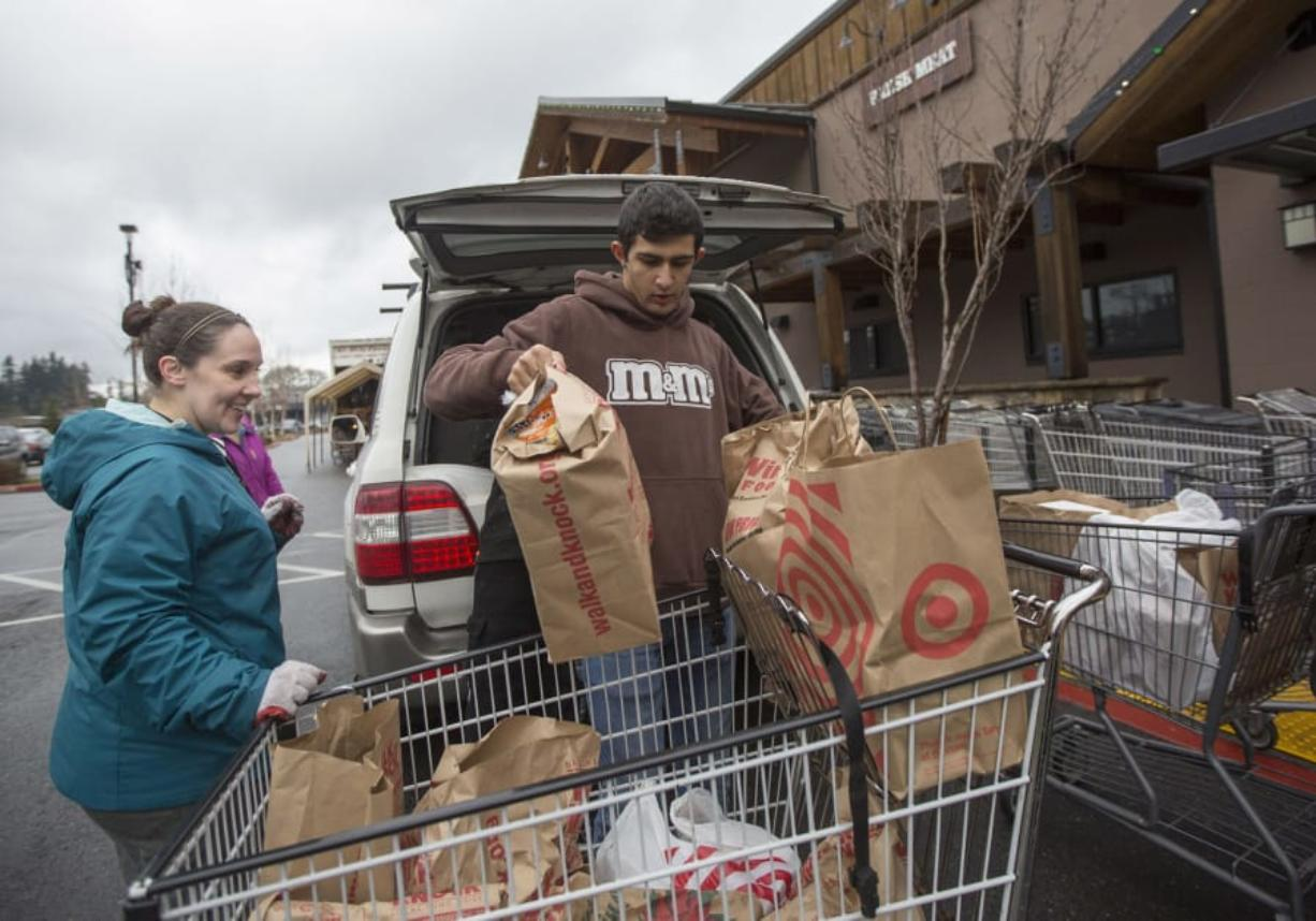 Volunteers Heidi Kartchner, left, and Noah Sarkissian help unload a car filled with Walk & Knock food donations in the parking lot at Chuck's Produce in Salmon Creek in December 2018.