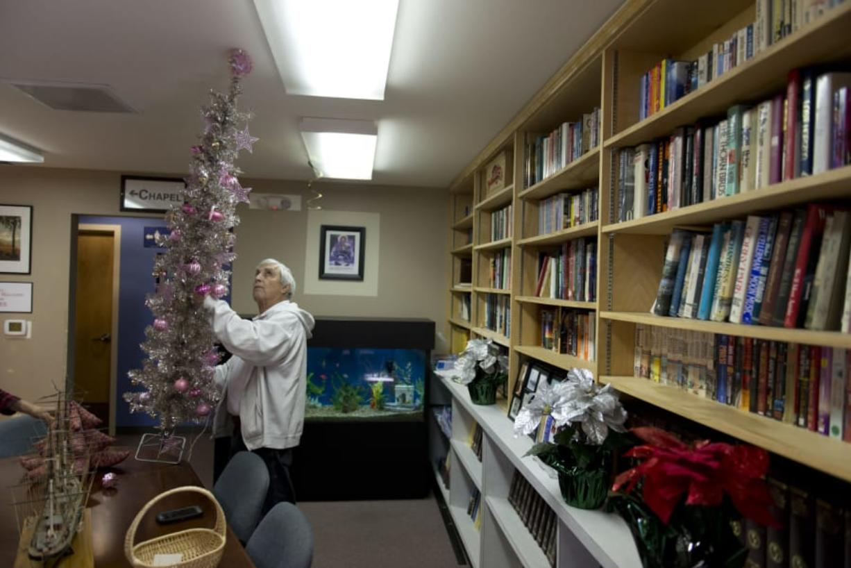 Anthony Moreno, a volunteer, installs a Christmas tree inside the library at the Fort Vancouver Seafarers Center. The center held its annual Christmas party Sunday, with about 50 people in attendance.