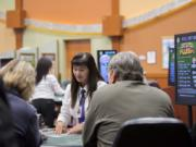 Dealer Sandy Pham looks over cards while assisting players at The Last Frontier Casino. The casino has about 200 employees.
