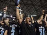 Hockinson coach Rick Steele and his team celebrate after winning their second straight 2A state football championship game on Saturday, Dec. 1, 2018, in Tacoma, Wash. Hockinson defeated Lynden 42-37.