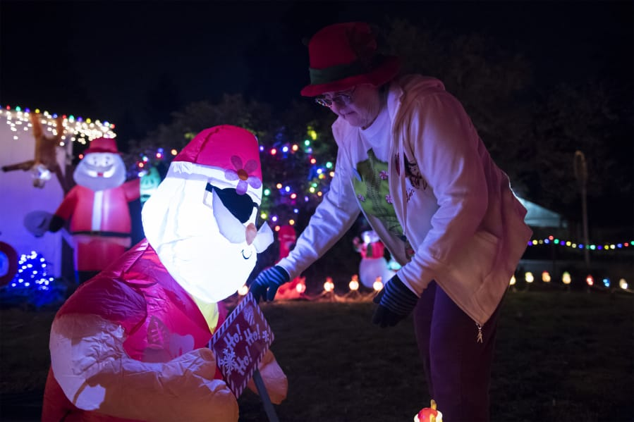 b8bdac163fd6 Cathy McGuire adjusts an inflatable Santa Claus at her home. Her yard is  filled with