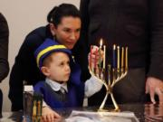 Four-year-old Ozzie Eichler lights a menorah with his mother, Julie Eichler, at the Chabad Jewish Center on Sunday, which was the last night of the eight-night Festival of Lights.