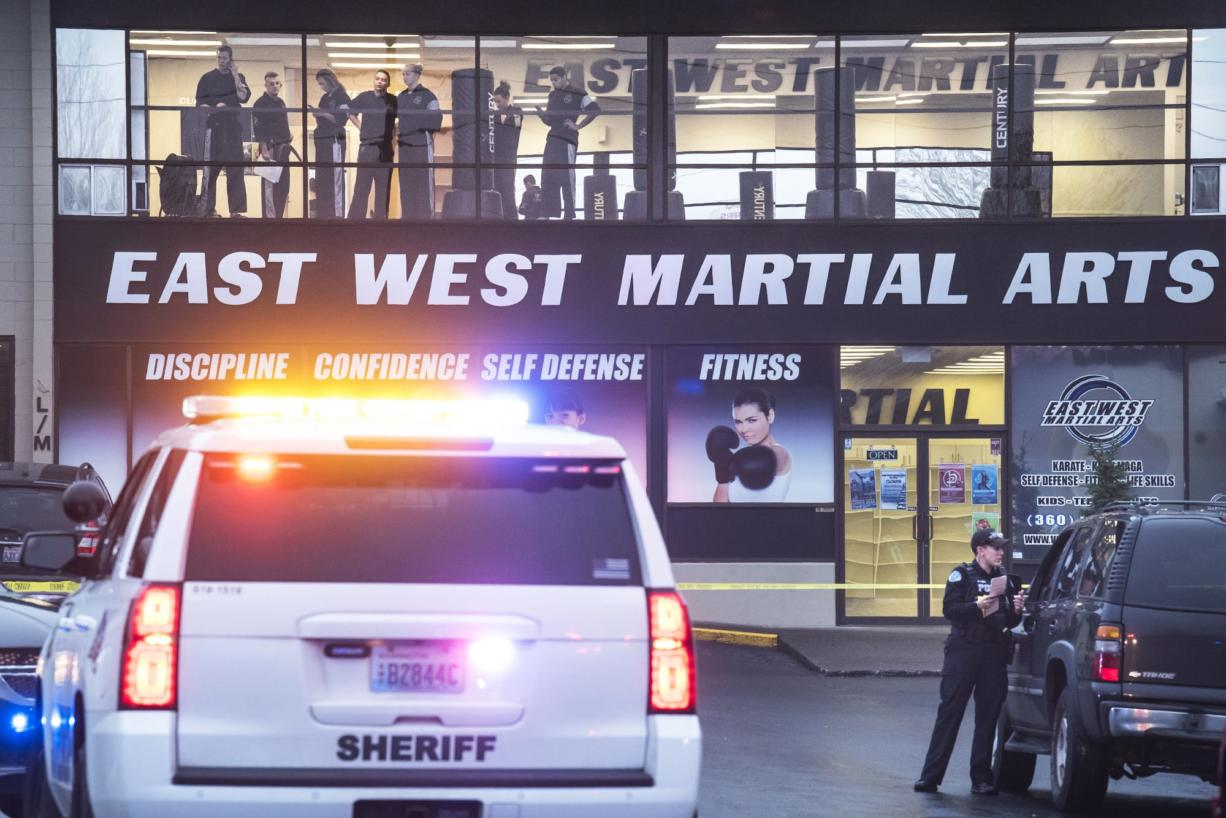 Spectators watch the investigation of a fatal shooting from the top floor of East West Martial Arts at the Pacific 63 Center in Hazel Dell on Monday afternoon, Dec. 10, 2018.