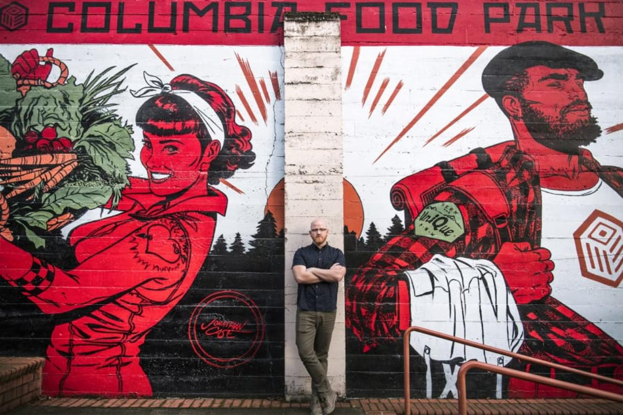 Alex Mickle, founder of the Columbia Food Park, stands in front of a new mural that adorns the eastern wall of the Columbia Food Park, painted by Portland artist Jonathan Case.