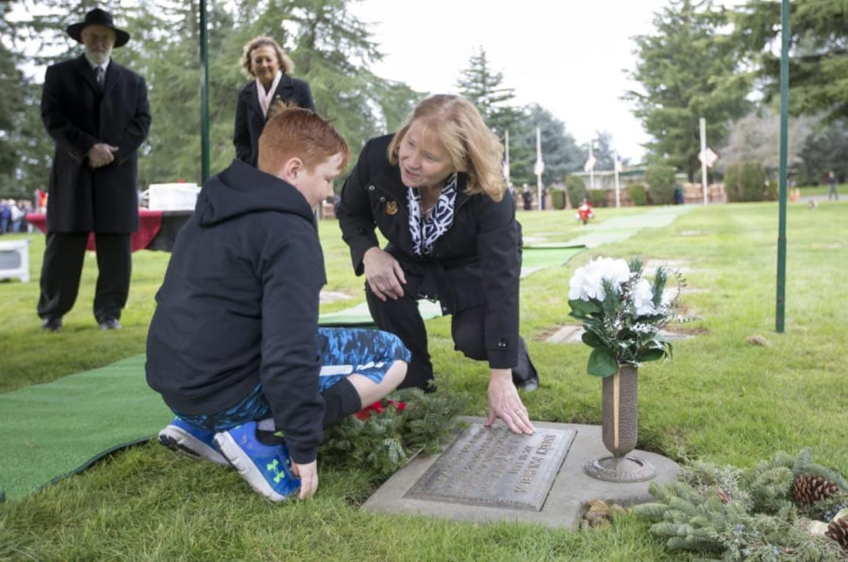 Vancouver Mayor Anne McEnerny-Ogle and Aiden Shields, place a wreath on the grave of Andrew Shields, at the National Wreaths Across America Day in Vancouver Saturday. Andrew Shields was a Battle Ground resident and combat medic killed in Afghanistan in 2008.