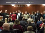 Under the gaze of families and supporters, Clark County Superior Court Judge David Gregerson, left, swears in (from left) Alishia Topper, Peter Van Nortwick, Chuck Atkins, Temple Lentz, Scott Weber and Julie Olson into their respective terms in office in Clark County government.
