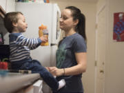 """Brodie Riggan, 2, drinks juice under the watchful eye of his mother, Kayla Stotts, on Friday night. Her two youngest sons spend the weekdays in child care, and Stotts said she tries to focus on her kids in the evenings. """"It's hard, because they want my attention. They've been without mom all day,"""" she said."""
