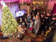 Vancouver police officers and firefighters pose for snapshots Sunday after delivering presents to the Pierro family, whose 6-year old daughter, Kierra, nearly died when she collapsed with cardiac arrest the weekend before Thanksgiving.