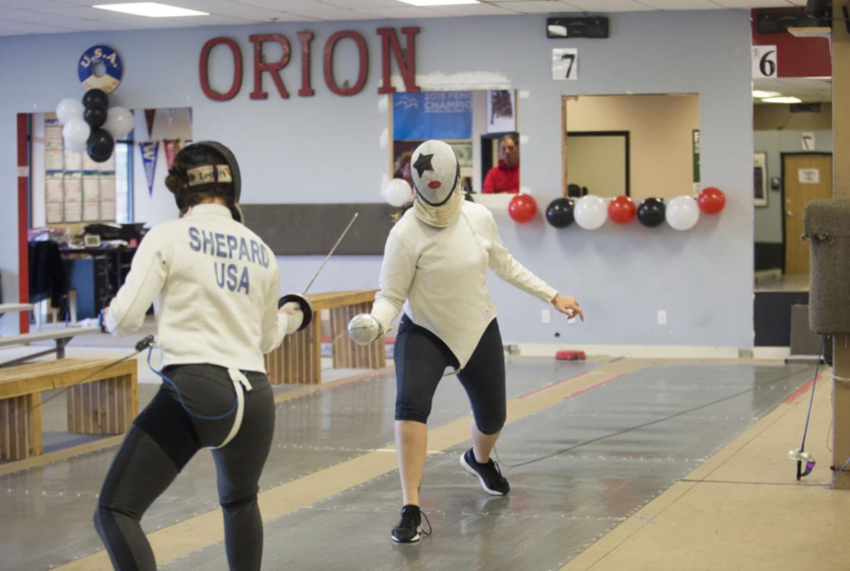 Jazzy Shepard, left, spars with Kaela Meeham at Orion Fencing on Sunday afternoon. Orion Fencing in Orchards held a free open house over the weekend. (Natalie Behring for The Columbian)