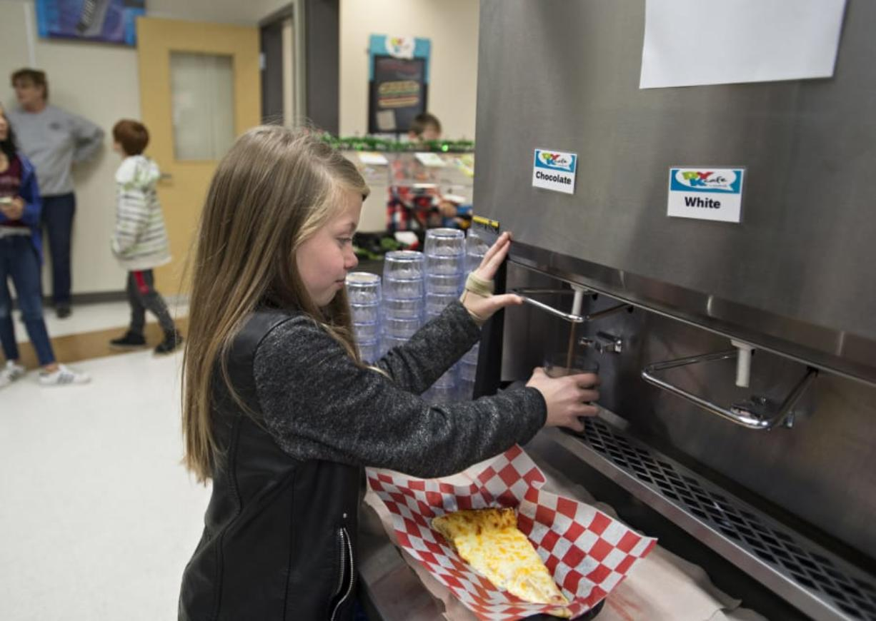 Fifth-grader Kelsey Bisconer, 11, fills up her glass with fresh chocolate milk during lunchtime Tuesday morning at Laurin Middle School. Clark County Green Schools received a $40,000 grant from the Washington Department of Ecology to install the dispensers at schools in Clark County.