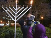 Ephraim Barstad holds up his daughter, Selah Barstad, 3, for a photo at the annual menorah lighting at Esther Short Park in 2017. The Chabad Jewish Center has held a public Hanukkah celebration in the park since 2004.