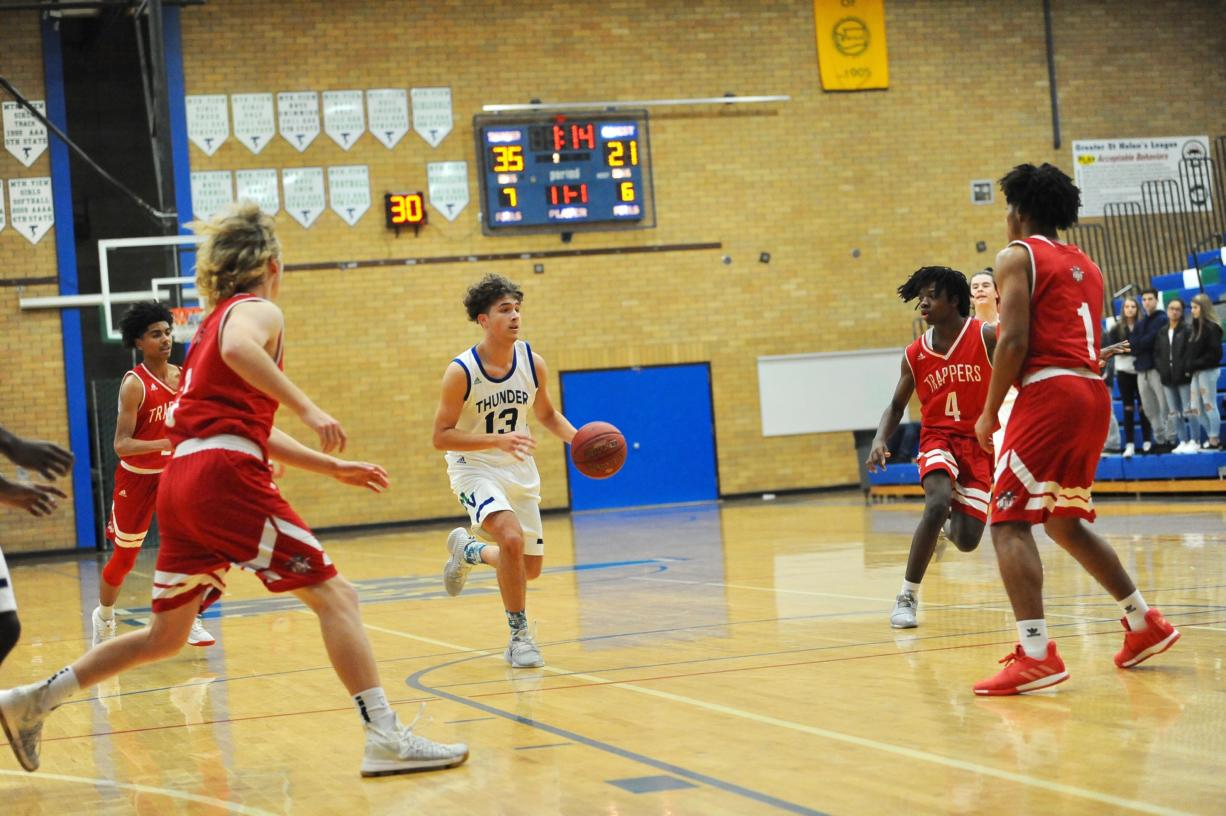 Four Fort Vancouver defenders collapse in the lane at Mountain View guard Sam Frosh drive to the hoop during the Thunder's 79-50 win on Tuesday night at Mountain View High School.