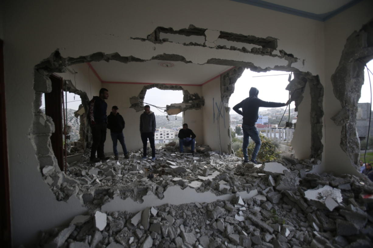 Palestinians examine a house after it was partially demolished by the Israeli army in the village of Shweikeh, near the West Bank city of Tulkarem, Monday, Dec. 17, 2018. The Israeli military has partially demolished the home of Ashraf Naalweh, a Palestinian accused of killing two Israelis in a West Bank attack two months ago.